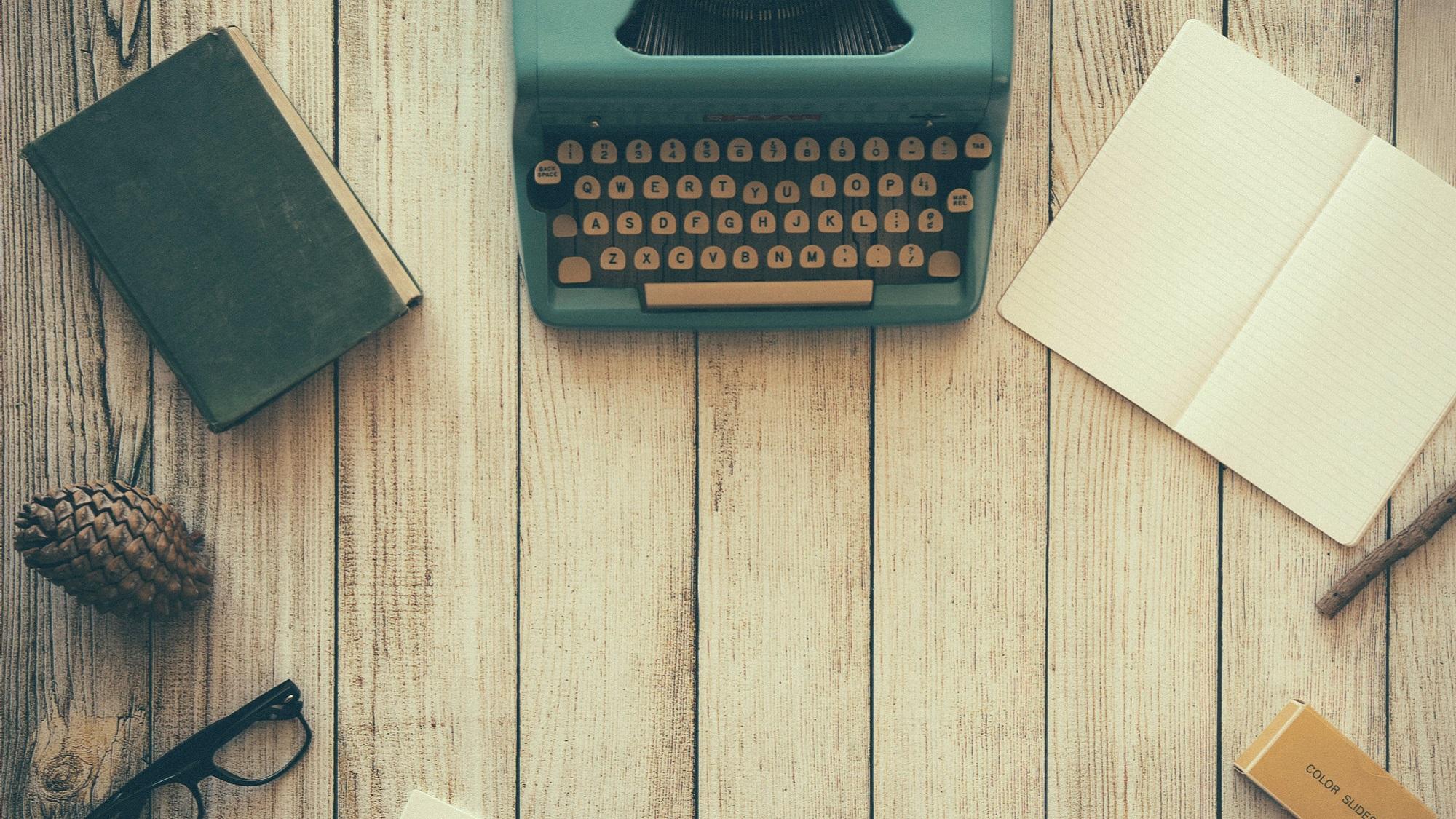 Jahresbericht MCM, Schreibmaschine, Notizbücher, Schreibmaterial auf Holztisch