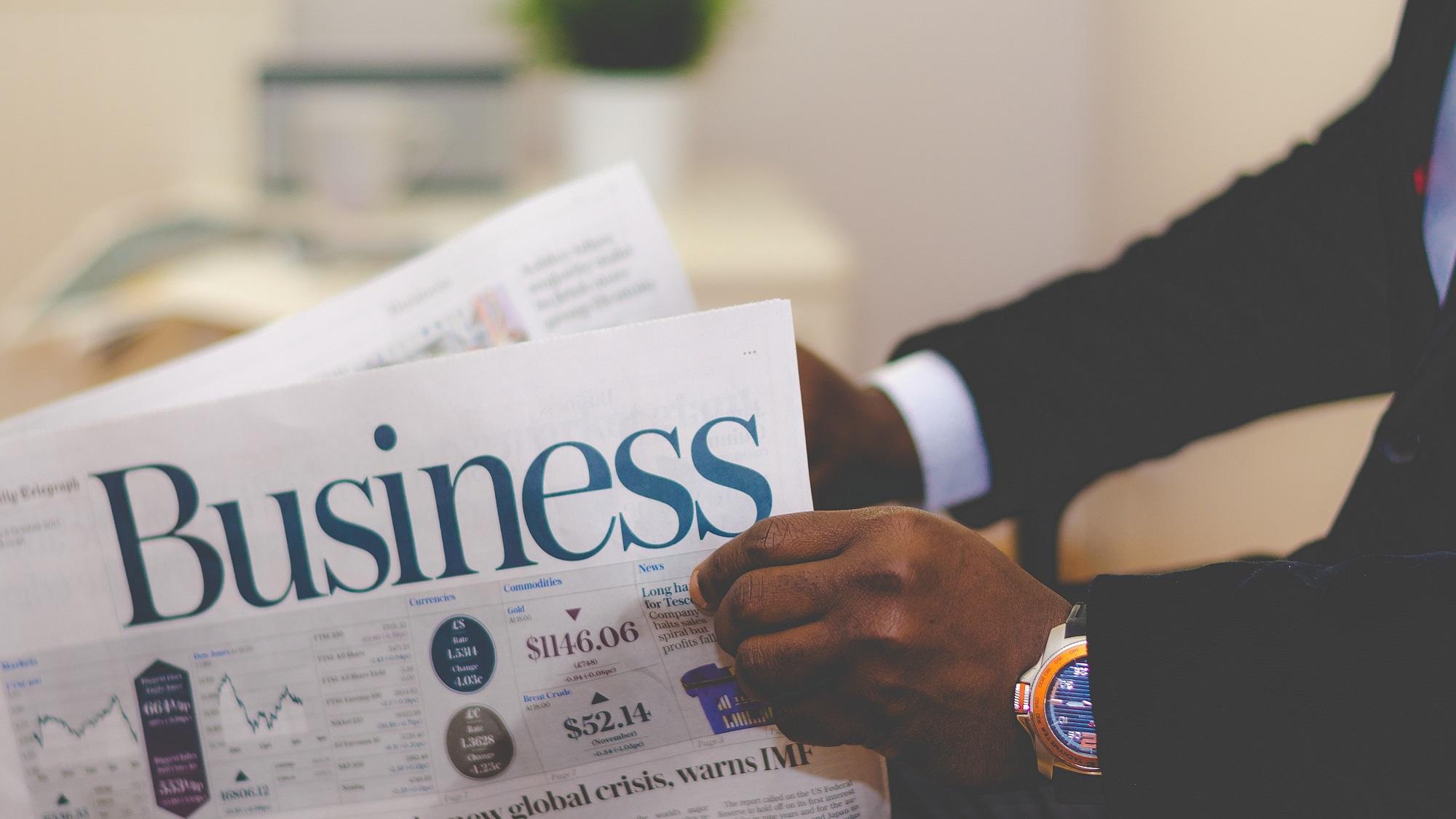 Mann in anzug liest Business Zeitung