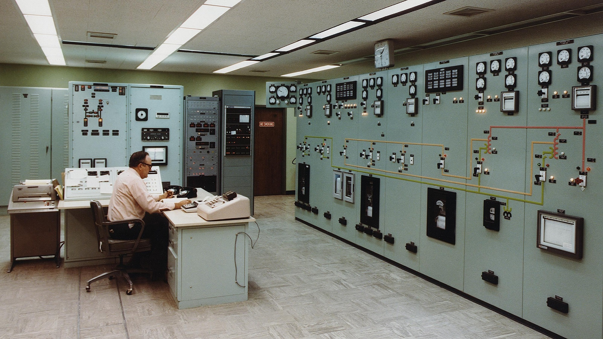 Man sits in control room made most probably in the mid 60ies
