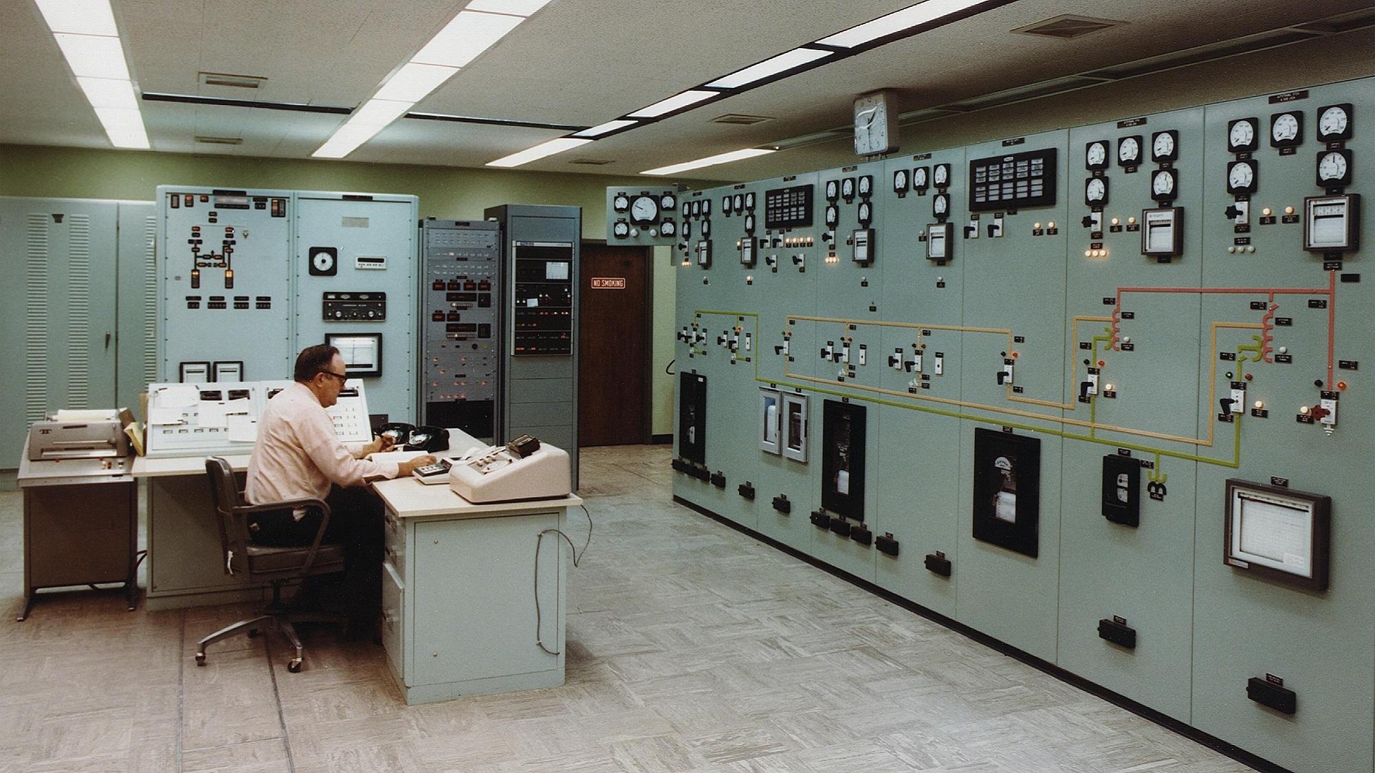 Mann sitzt in altem Kontrollraum aus den 60ern