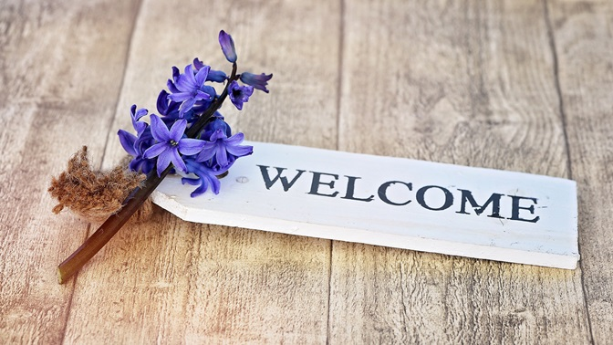 """""""Welcome"""" sign on wooden floor with real blue flowers"""