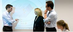 Vier Personen diskutieren ein projeziertes Slide