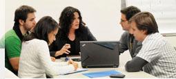 Fünf Personen sitzen diskutierend um einen Computer