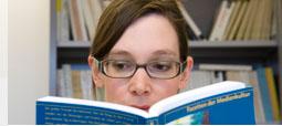 Eine Frau, die in einem Buch liest.